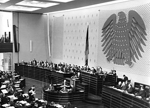 Coat of arms of Germany - The Bonn-Paris conventions, which granted West Germany limited sovereignty and NATO membership, are being discussed in the federal parliament in Bonn. The room is decorated with the Federal Eagle designed by Ludwig Gies, which now hangs in the present-day plenary hall in the Reichstag building in Berlin.