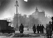 Photo noir et blanc sur laquelle le Reichstag, partiellement caché par une rangée d'arbres, est visible en arrière-plan, le 28 février 1933, lendemain de son incendie. Quelques badauds, en habits sombres, se tiennent debout au premier plan.