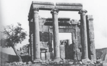 A frontal black and white picture of ionic temple ruins showing a massive entrance door and a smaller side door. Two children in head covers sit at the right of the temple facade.