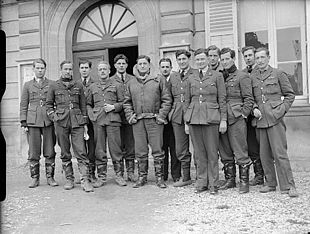 Thirteen men in dark military uniforms standing outside a building