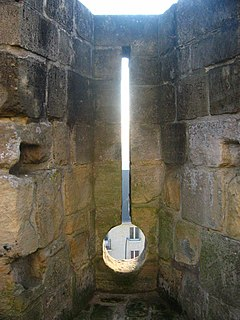 Embrasure opening in a crenellation or battlement between the two raised solid portions or merlons