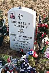 A military grave stone with an image of a man with a cross next to it. Also shows the name of the individual and info about them with an image of the Medal of Honor.