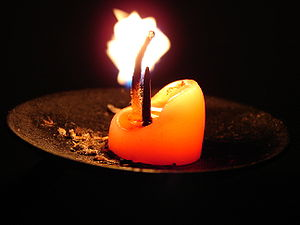 An almost burnt-down lit candle on a candle ho...