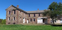 A large L-shaped stone house with missing windows and a tree to the right
