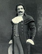 Мужчина с темными волосами и вьющимися усами стоит в позе.  На нем длинное пальто с кружевом на шее и манжетах.