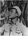 Chinese workman at the U.S. Army 14th Air Force Headquarters uses the neck of the discarded light bulb for a drinking... - NARA - 196229.tif