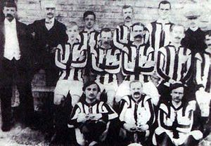 11 men in 3 rows, dressed in black-and-white striped football kit with 3 other men in suits