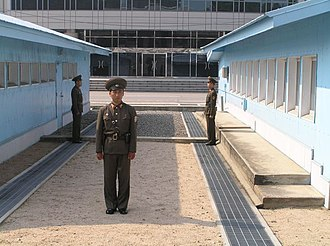 Joint Security Area - DPRK soldiers standing guard at the JSA between the blue buildings. View from the north. To the south: the ground floor of Freedom House, in South Korea.