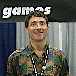 A Caucasian man with short brown hair and a convention pass on a lanyard around his neck smiles for a camera. Part of the Telltale Games logo is visible in the background.