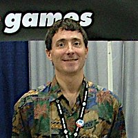 "A man wearing multicolored shirt smiles at the camera. Behind him stands a blue and white background, above which is an excerpt of logo which reads ""games""."