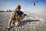 Defense.gov News Photo 111230-M-PH073-126 - U.S. Marine Corps Cpl. William Cox shields himself from flying rocks and sand as an MV-22 Osprey aircraft prepares to take off in Nimroz province.jpg