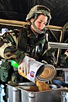 Defense.gov News Photo 120310-Z-BR512-070 - U.S. Air Force Airman 1st Class Kristen Patterson with the 140th Force Support Squadron prepares food to be served at a simulated deployed single.jpg