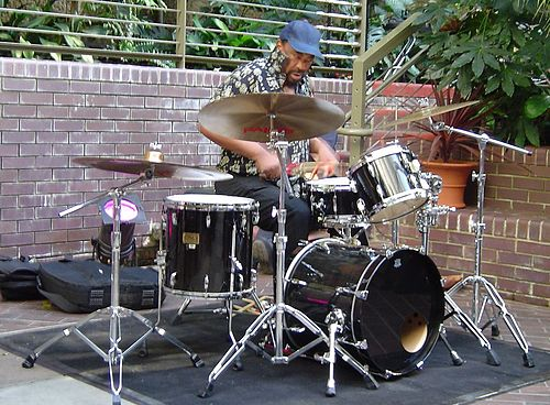 "South African jazz drummer Louis Moholo playing a four-piece kit. One of the conventions of drum kit playing is that the number of ""pieces"" in a kit only counts the drums, not the cymbals or other percussion instruments. Drumming 2.jpg"