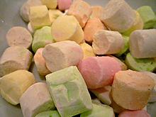 A pile of small cylindrical pieces of confectionery each one a different pale pastel colour
