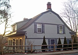 A gray wooden house seen from the side, lit by a setting sun from the left. Its roofline curves in segments, with a brick chimney at the crest. The upper section has wood shingled siding in a scale pattern.