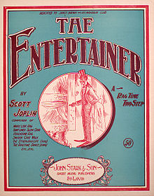 The front cover of The Entertainer sheet music. It has a green background and in the centre is a red ink drawing of a stereotyped African-American performer on stage in top hat and tails