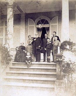 A group of people assembled on a columned porch at the top of a flight of steps, with one older woman seated, one younger woman leaning on the arm of an older bearded man, two younger men, and three small boys