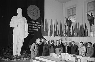 Socialist realism - Workers inspect architectural model under a statue of Stalin, Leipzig, East Germany, 1953.