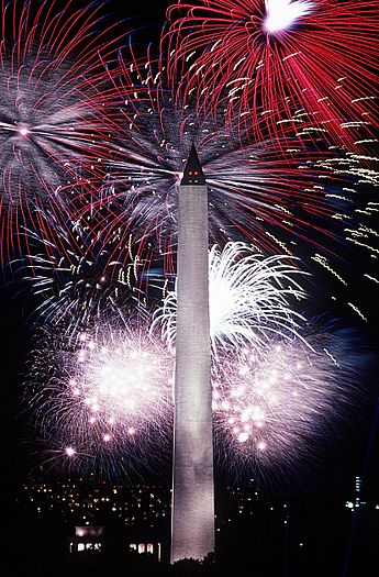 Photograph of red, white, and blue fireworks lighting the night sky behind the Washington monument in 1986
