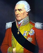 White haired man with red military jacket, decorated in yellow, with fancy epaulets on his shoulders, a ribbon sash, and military decorations.