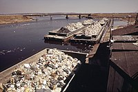 GARBAGE SCOWS FROM MANHATTAN WAIT TO BE UNLOADED AT THE STATEN ISLAND LANDFILL - NARA - 549801.jpg
