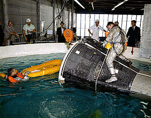Gemini 3 - Young atop a Gemini spacecraft with Grissom in the water at left at the Manned Spacecraft Center during water egress training