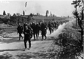 Soldiers marching down a road