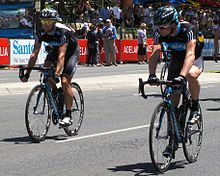 A pair of cyclists on the road, wearing matching black jerseys with steel blue trim. Spectators are visible on the roadside and behind barricades.