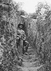 A man in military uniform sitting down in a trench. On both sides are walls of dirt, with sandbags on top.