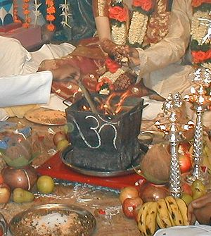"Throwing offerings on the fire, lit in a box with a Devanagari ""Aum"" written on it, during a Hindu wedding."