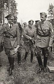 Photo noir et blanc prise le 4 juin 1942. Au premier plan, debout dans l'herbe, Adolf Hitler en uniforme (à gauche) et le maréchal finlandais, Carl Gustaf Emil Mannerheim (à droite), discutent. Au centre, au second plan, un officier allemand, entouré de quelques autres militaires, les suit. Le ciel, en arrière-plan, est clair.