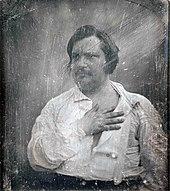 Portrait photographique en noir et blanc d'un homme moustachu portant chemise blanche ouverte, main droite sur le cœur.