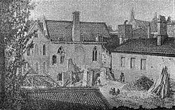 Een zwart-wit afbeelding van verschillende korte gebouwen geclusterd in een kleine ruimte.  Een tuin op de voorgrond is gevuld met afval.