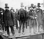 A group of ten men in nineteenth century dark suits, wearing top hats, observing something behind the camera