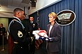 Jake Johnson, deputy director for Pentagon tours, presents the official flag of the assistant secretary of defense to Victoria Clarke after she was sworn in as ASD for public affairs.jpg