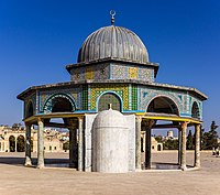 A gray metal-domed octagonal structure decorated with tiles of different colors and geometric designs, supported by dark stone columns with beige-colored capitals