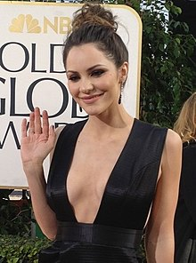 Katharine McPhee is pictured outdoors with her right hand up slightly waving with a small smile not showing teeth; Her long dark hair with lightened tips is up in a messy bun.  She is wearing a little black dress with a plunging neck line.