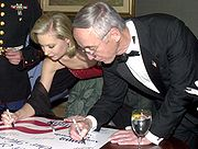 Miss America 2002, Katie Harman signs a USO poster, while performing her community service work
