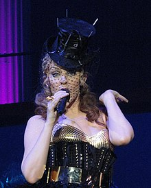 A woman with dark-blonde hair is standing in front of a dark blue and black background with a mic in her hand. She is wearing a metallic golden top, a large black crinoline, a belt and a top hat. A netted veil is covering her face.