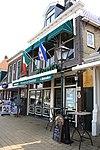 foto van Tot winkel verbouwd pand met verdieping en forse kroonlijst onder zadeldak met voorschild waarboven topschoorsteen