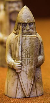 Photograph of an ivory gaming piece depicting an armed warrior