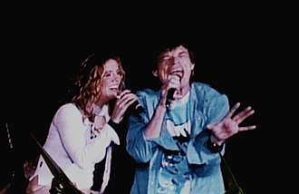Sheryl Crow - Crow and Mick Jagger on stage during a Rolling Stones concert in 2002
