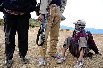 Nepalese Civil War - Three Maoist rebels wait on top of a hill in the Rolpa district for orders to relocate