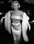Photograph of a blonde woman wearing a glamorous dress, a fur scarf, and gloves