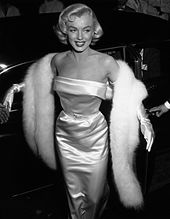 An almost full-body shot of Monroe in a figure-hugging light-colored strapless dress with a white fur stole and long white gloves. She is glancing to her left while smiling.