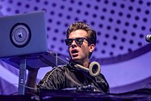 Mark Ronson onstage wearing sunglasses, infront of a purple background.