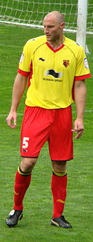 A man wearing a yellow shirt, red shorts, red socks and black football boots, standing on a grass field