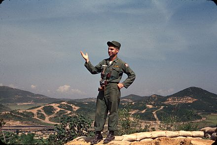Dukakis off duty at a gun emplacement overlooking UN Command Military Armistice Commission base camp at Munsan-ni Korea 1956. Michael Dukakis Korea 1956.jpg