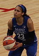 Young woman in long ponytail and gray uniform carries the ball while guards from opposing team try to stop her or else stop and watch