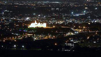 Mysore palace lit up, seen from Chamundi hill.jpg